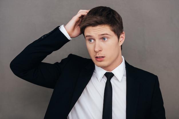 Non ne è sicuro. giovane frustrato in abiti da cerimonia che tiene la mano tra i capelli e distoglie lo sguardo mentre sta in piedi su uno sfondo grigio gray