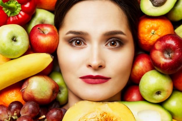 Testa di una bella giovane donna si trova in un mucchio di vari frutti luminosi. alimentazione sana e vegetarismo.