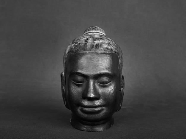 Testa di buddha, colore nero scolpita in pietra su parete scura. il volto dell'antico buddha in pietra, vista frontale.
