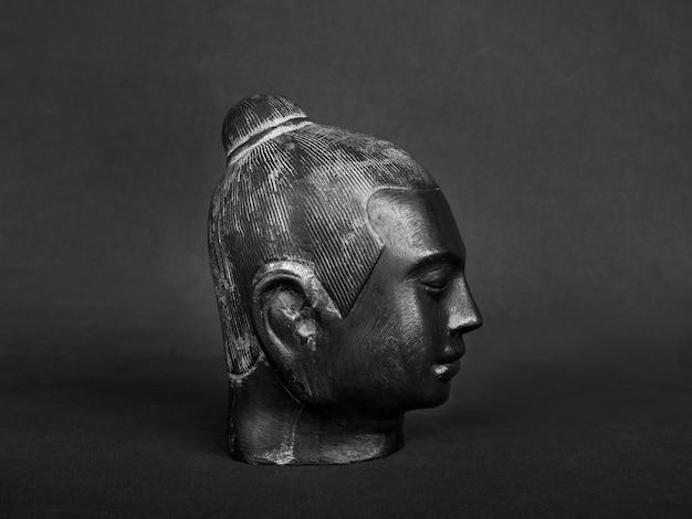 Testa di buddha, colore nero scolpita in pietra su parete scura. il volto dell'antico buddha in pietra, vista laterale.