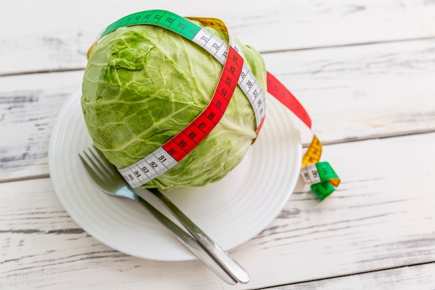 Testa di cavolo con nastro adesivo di misurazione su un piatto su un fondo di legno. dieta e controllo del peso. vista dall'alto.