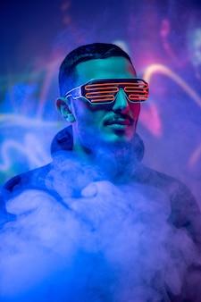 Capo di un giovane uomo contemporaneo di razza mista con occhiali a spirale rossi tra fumo e luci al neon blu