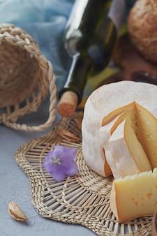 Una testa di formaggio fresco biologico servito con pane, noci, vino bianco e fiori di campana blu. ã?rganic concetto di cibo.