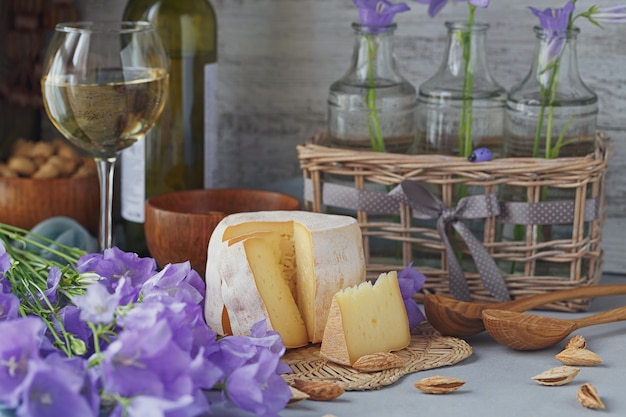 Una testa di formaggio fresco biologico servito con pane, noci, vino bianco e fiori estivi. concetto di cibo sano e biologico.