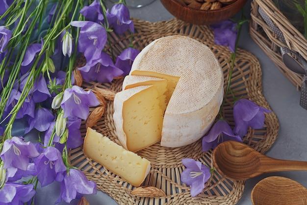 Una testa di formaggio fresco biologico servito con pane, noci, vino bianco e fiori estivi.
