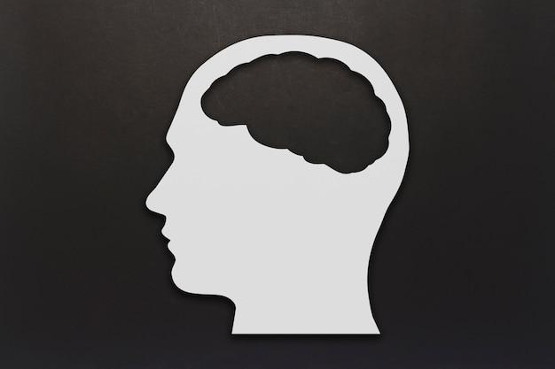 Testa fatta di cartone bianco con un cervello su sfondo nero. copia spazio. vista piana, vista dall'alto.