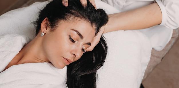 Sessione di massaggio alla testa con un'affascinante signora bruna sdraiata sul divano della spa con gli occhi chiusi