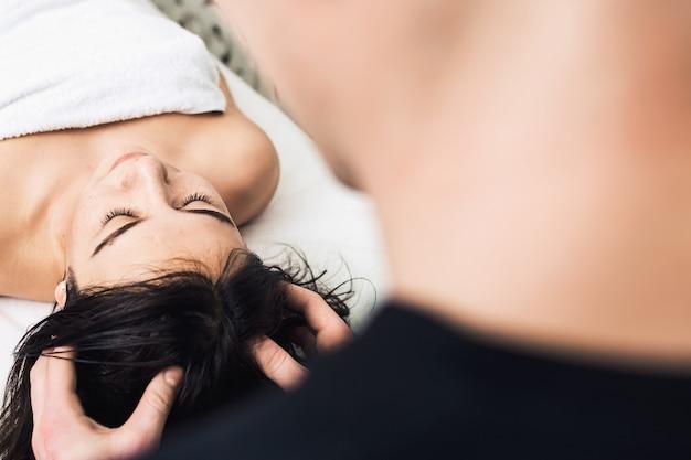 Massaggio alla testa nella spa. clinica cosmetologica, spa, benessere, concetto di assistenza sanitaria.