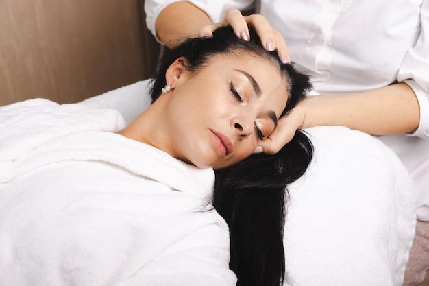 Massaggio alla testa per donna al salone della stazione termale trattamento di ringiovanimento assistenza sanitaria bellezza pelle viso femminile