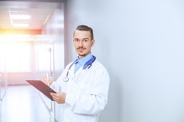 Colpo alla testa vicino sorridente terapista medico maschio. giovane medico con lo stetoscopio nella hall dell'ospedale