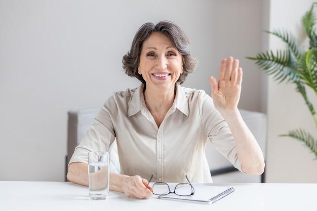 Colpo alla testa ritratto caucasico invecchiato donna d'affari fa videochiamata guarda la fotocamera e sorridente, felice leader senior mostra gesto di saluto dipendente alla riunione online, assunzione tramite videoconferenza