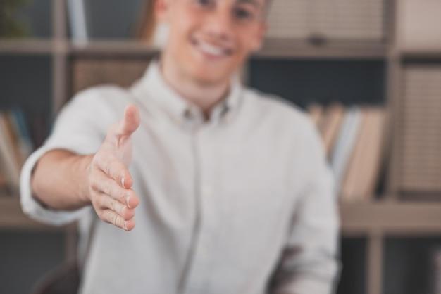 Colpo alla testa ritratto sorridente uomo d'affari con gli occhiali che estende la mano per la stretta di mano alla macchina fotografica, amichevole responsabile delle risorse umane che saluta il candidato al colloquio, offrendo un accordo, accogliendo il cliente alla riunione