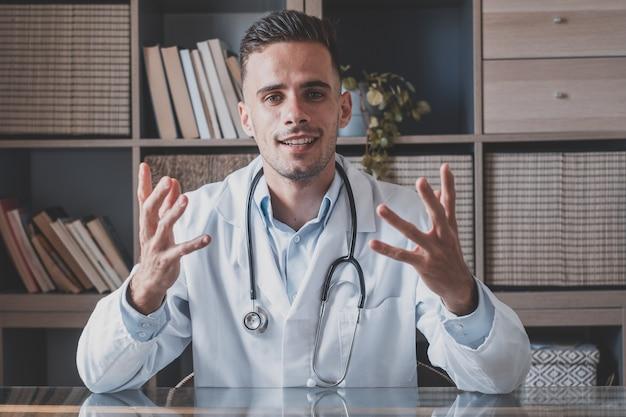 Colpo alla testa ritratto giovane medico con gli occhiali e l'uniforme bianca con lo stetoscopio che parla, consultando il paziente online, guardando la fotocamera, facendo videochiamate, seduto al tavolo in ufficio