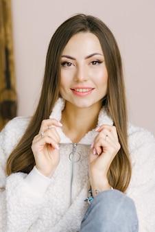 Una foto alla testa di una bella donna con gli occhi scuri, lunghi capelli castani e un sorriso tenero e felice. donna felice, ragazza felice
