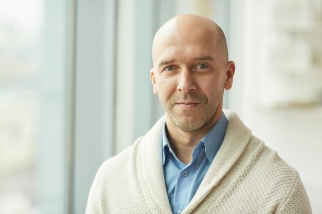 Testa e spalle ritratto di calvizie uomo maturo che indossa cardigan mentre in piedi dalla finestra in ufficio bianco, copia dello spazio