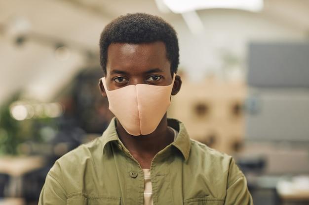Testa e spalle ritratto di fiducioso afro-americano uomo che indossa la maschera in ufficio e mentre si trovava in ufficio, copia spazio