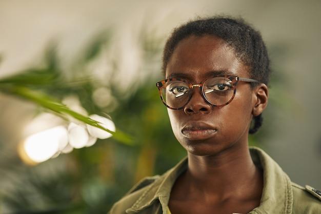 Testa e spalle ritratto di donna afro-americana contemporanea con gli occhiali e in piedi in un ufficio moderno con piante, copia spazio