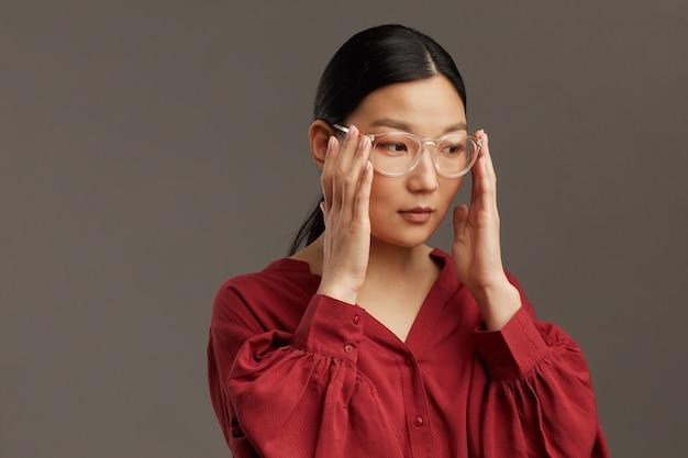 Testa e spalle ritratto di donna asiatica elegante che indossa gli occhiali mentre in piedi contro il muro grigio, copia dello spazio