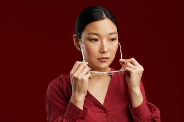 Testa e spalle ritratto di donna asiatica elegante che indossa gli occhiali mentre in piedi contro il muro marrone rossiccio, copia spazio