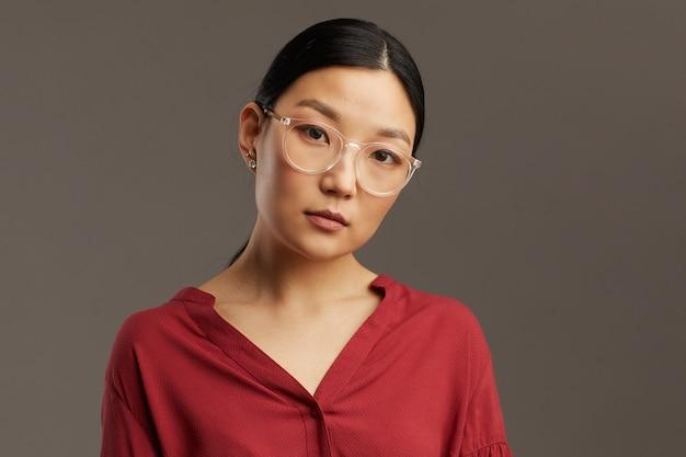 Testa e spalle ritratto di elegante donna asiatica con gli occhiali mentre in piedi contro il muro grigio, copia dello spazio