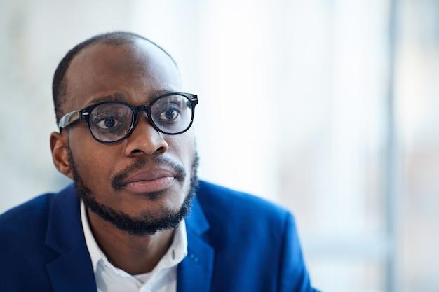 Testa e spalle ritratto di riuscito imprenditore afro-americano con gli occhiali guardando il partner sul tavolo durante la riunione, copia dello spazio