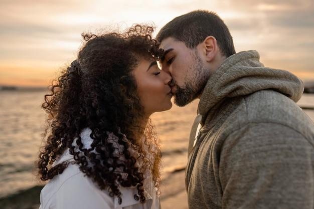 Ritratto di testa e spalle di giovane bella coppia innamorata che bacia al tramonto in località balneare invernale con cielo nuvoloso.