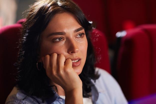 Testa e spalle ritratto di giovane donna che piange al cinema mentre si guarda un film drammatico triste, copia spazio