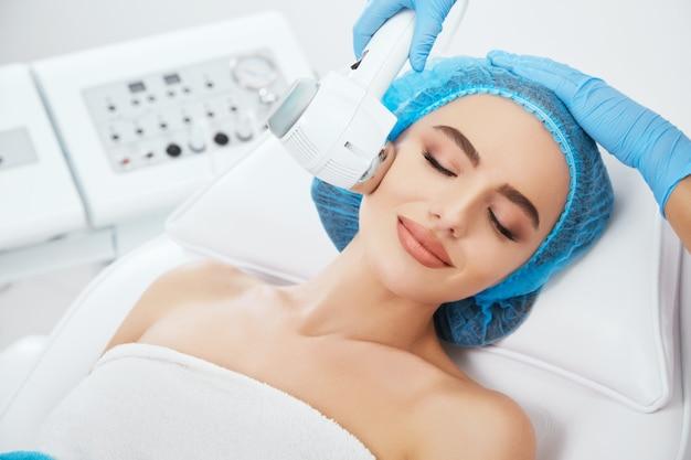 Testa e spalle di donna sdraiata sul divano in protezione blu in clinica cosmetologica con gli occhi chiusi e sorridente. medico che tiene il martello caldo / freddo della spa vicino al suo fronte
