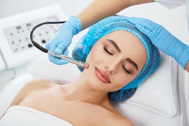 Testa e spalle di donna sdraiata sul divano in protezione blu in clinica cosmetologica con gli occhi chiusi e sorridente. mani del medico in guanti blu che tengono strumento per microdermbrasia vicino al suo viso