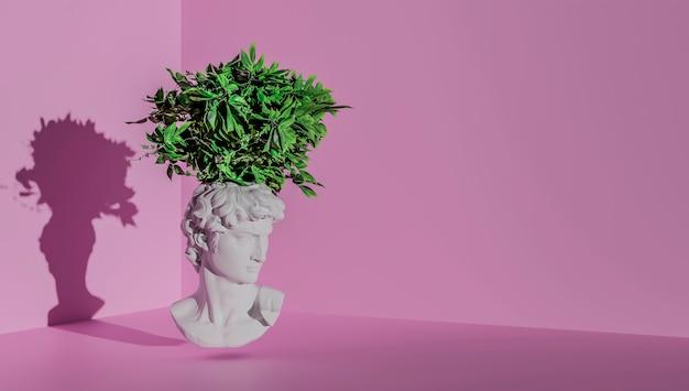 Testa di una statua di david su sfondo rosa con piante sulla testa.