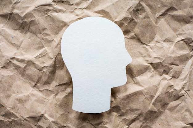 Simbolo della testa su sfondo di carta stropicciata, idea di salute mentale e psicologia