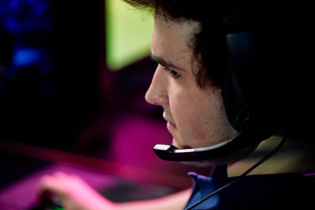 Capo del giovane operatore di call center in cuffia che consulta uno dei clienti o un giocatore di videogiochi e-sport seduto davanti allo schermo del computer