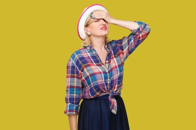 Mal di testa, errore o problema. ritratto di triste donna matura alla moda delusa in stile casual con cappello in piedi con la mano sulla fronte e sconvolto. studio al coperto colpo isolato su sfondo giallo.