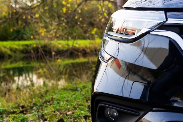 Faro di una moderna automobile nera in una corsia di parcheggio vicino a uno stagno in un parco, trasporto sicuro per la ricreazione con un'auto nel concetto di natura