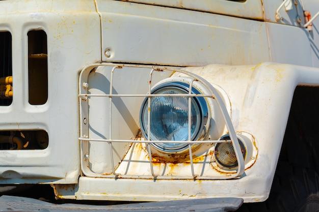 Faro di un vecchio camion sovietico arrugginito