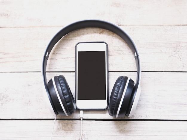 Cuffia e telefono cellulare su di legno bianco