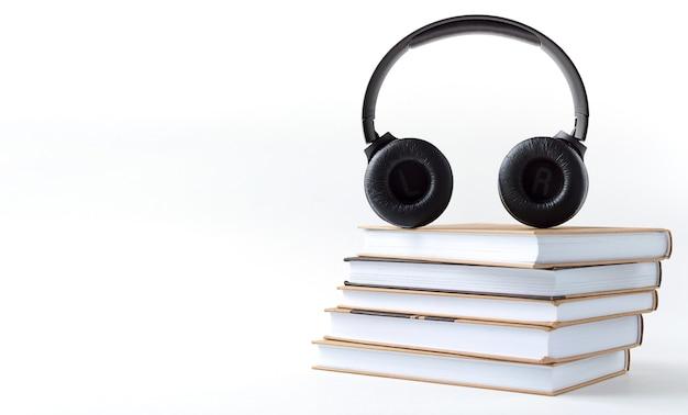 Cuffie e libri su uno sfondo bianco. concetto di audiolibro con copia spazio.