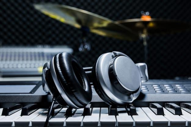 Cuffie su sfondo di pianoforte elettrico sullo sfondo di strumenti musicali.