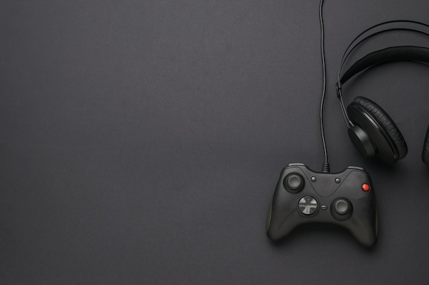 Cuffie e una console di gioco su sfondo nero. un dispositivo per giocare ai giochi per computer. disposizione piatta. posto per il testo.