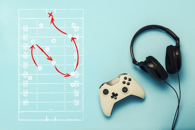 Cuffie e gamepad su uno sfondo blu. aggiunto disegno con le tattiche del gioco. football americano. il concetto di giochi per computer, intrattenimento, giochi, tempo libero. vista piana, vista dall'alto.