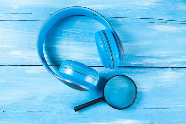 Cuffie e lenti di ingrandimento. concetto di ricerca di file audio su superficie di legno blu