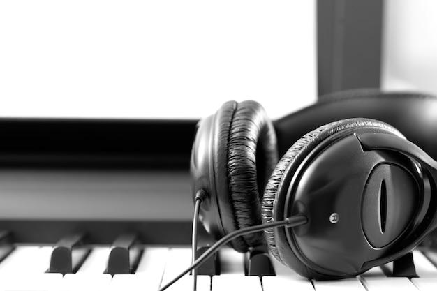 Cuffie sulla tastiera del sintetizzatore musicale. cuffie sul pianoforte elettronico. sottofondo musicale