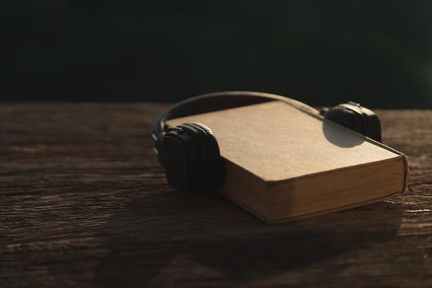 Cuffie e vecchio libro su legno