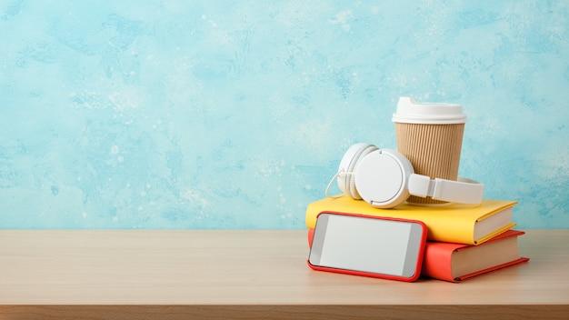 Cuffie, smartphone, pila di libri e bicchiere di carta su un tavolo