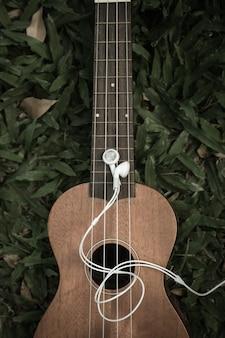 Cuffie e ukulele sull'erba. concetto di musicoterapia