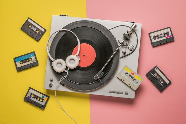 Cuffie su lettori di vinile e cassette sparse su rosa e giallo. dispositivi retrò per memorizzare e riprodurre registrazioni audio.