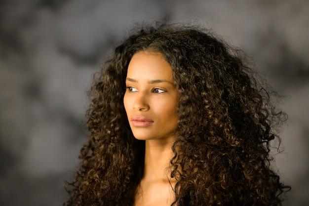 Primo piano del volto di una bella ragazza nera premurosa con capelli ricci lunghi