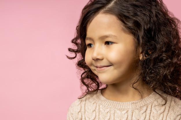 Ritratto del primo piano del primo piano del volto del bambino affascinante, bambina con capelli ricci scuri, pelle marrone, occhi marroni, maglione beige da portare, carino che sorride delicatamente e che osserva da parte.