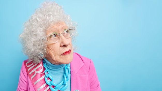 Il colpo alla testa di una donna anziana dai capelli ricci concentrata da parte ha un'espressione premurosa il viso rugoso indossa occhiali per una buona visione indossa abiti festivi
