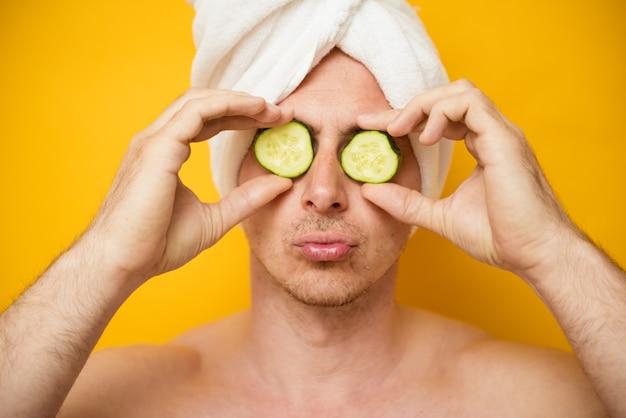 Colpo alla testa di un ragazzo divertente, copre gli occhi con fette di cetrioli, ha trattamenti termali, pose al coperto. uomini, bellezza, concetto di cosmetologia